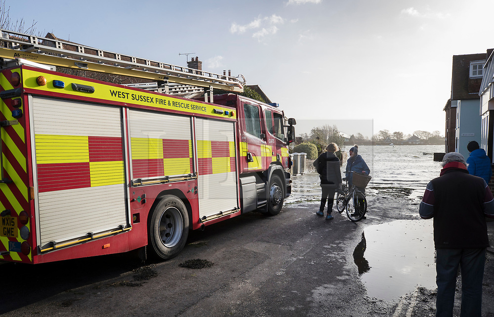 © Licensed to London News Pictures. 03/01/2018. Bosham, UK. A fire engine keeps an eye on rising tidal flood water at Bosham as storm Eleanor hits the south. Winds of up to 80 mph are being forecast today in parts of the UK. Photo credit: Peter Macdiarmid/LNP