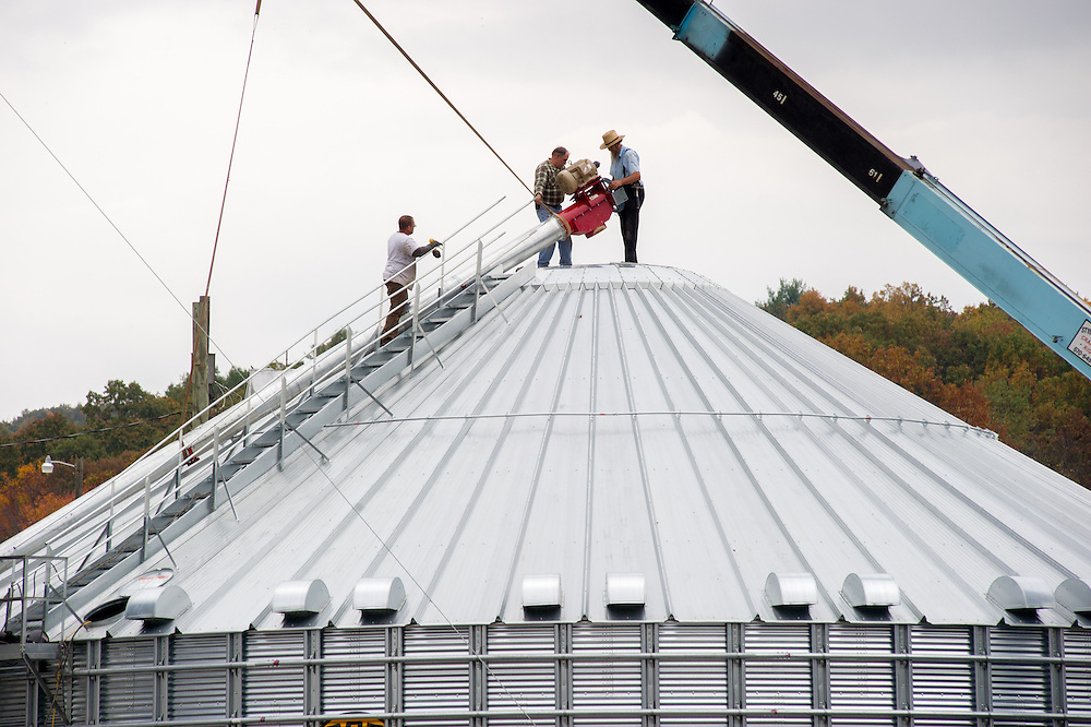 Farmer's setting up steel grain silo for harvest in Dalmatia, Pennsylvania, USA