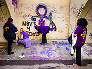 21 APRIL 2017 - CHANHASSEN, MN: Women draw graffiti and write notes honoring Prince in the pedestrian tunnel in front of Paisley Park, his former home and recording studio. The tunnel has become a memorial to Prince, people have drawn graffiti in the tunnel honoring him and they leave memorials in the tunnel. The superstar died from an accidental overdose of the opioid fentanyl on April 21, 2016. Friday was the first anniversary of his death. Crowds of people gathered at Paisley Park, which is now a museum, to honor the Minnesota born musician.     PHOTO BY JACK KURTZ