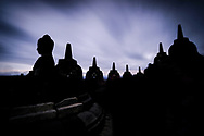 Silhouette of Buddhist stupas stand out in the sky before dawn in the Borobudur temple of Java, Inonesia. Photo by Lorenz Berna