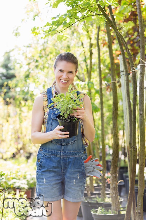 Portrait of happy woman holding potted plant at garden