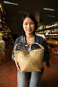Salesgirl in one of the Battrang pottery showrooms holds a basket of items she has just sold.  She is seated in the salesroom, shelves of ceramic items visible beyond her.