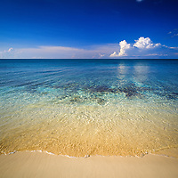 The clear ocean gently lapping onto a sandy beach with a coral reef close to the shore.