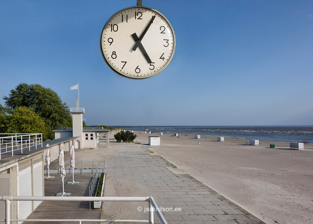 Hanging clock and balustrade. Empty beach in Pärnu, Estonia.