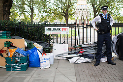© Licensed to London News Pictures. 07/10/2019. London, UK. A police officer stands next to a pile of confiscated equipment after an Extinction Rebellion Roadblock was removed on Millbank . Photo credit: George Cracknell Wright/LNP