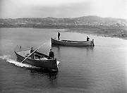 """14-15/ 05/ 1959<br /> 05/14-15/1959<br /> 14-15 May 1959<br /> Back to the quiet of Ard Thiar Quay near Carna, Co. galay, these Gael Linn boat owners prepare to come ashore. They are Seosamh O Connaighle and his helper Sean Og Mac Donnchadha in the """"Cailin"""" (left) and Sean Mac Donnchadha and his son Seosamh in the """"MacDara""""."""