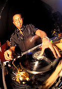 A black DJ adjusts a record on the turntables, U.K, 2000s.