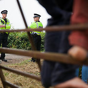 Police on patrol outside the gates of the camp. Reclaim the Power camp is set up in a field near Balcombe. The site is squatted but so far nor the owner nor police has made any moves to stop the camp from setting up. It is organised by the environmental group No Dash for Gas and the movement is protesting against the company Cuadrilla's fracking testing near Balcombe and have come to Balcombe to lend its support to the local protests against the drilling for gas.