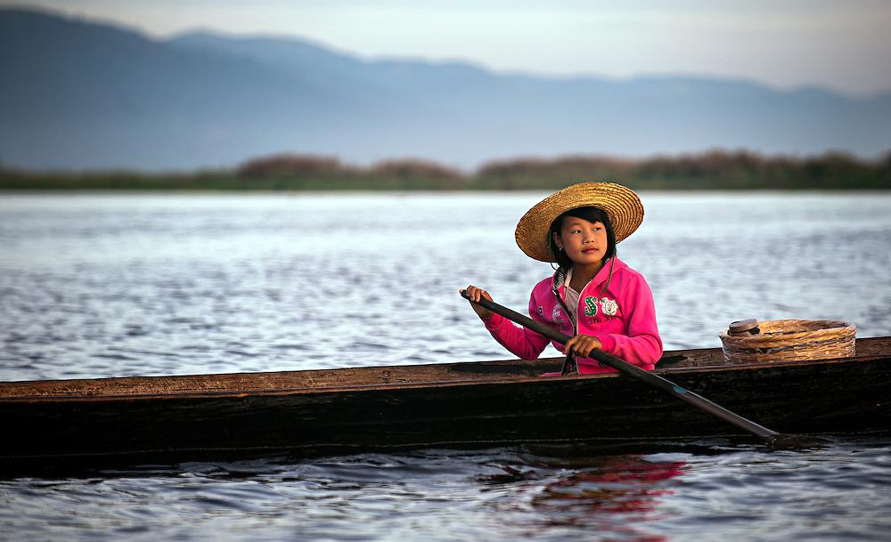 A girl fishing at sunrise on Inle Lake, Myanmar.