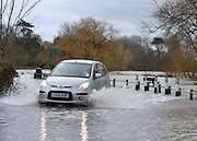© Licensed to London News Pictures. 29/12/2012. Laleham, UK. A car ignores road closed signs and drives along a road next to the flooded River Thames in Laleham.  Flooding along the River Thames today 29th December 2012.Forecasters say the UK can expect heavy rain and winds the coming days. Photo credit : Stephen Simpson/LNP