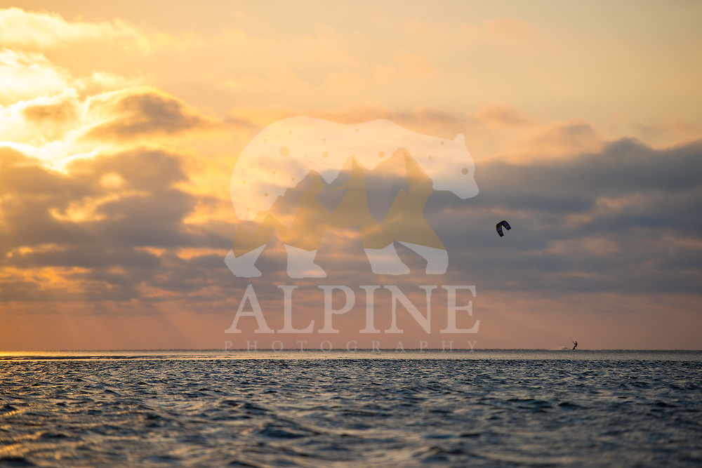 An outdoor athleteg as seen kitesurfing on a sunny and windy evening at the North Sea, near the bay of Lauwersoog, Groningen, the Netherlands.