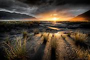 Alaska's Turnagain Arm reflects the light of the setting sun across silt-covered earth.