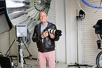 Portrait of happy senior photographer with camera and equipments in studio