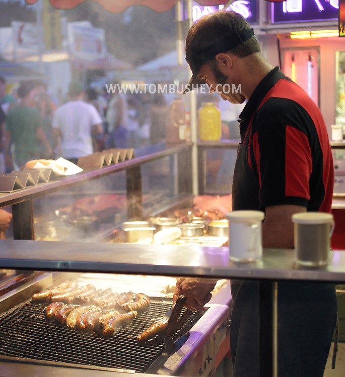 Augusta, New Jersey - A man cooks sausages in a refreshment stand at the New Jersey State Fair and Sussex County Farm and Horse Show on Aug. 11, 2010.