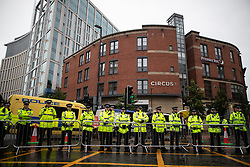 © Licensed to London News Pictures . 29/09/2019. Manchester, UK. Dozens of police ring the conferece perimeter as the demonstration passes . Thousands attend a march for the People's Assembly . Demonstrations for and against Brexit , austerity measures , the environment and numerous social issues take place across Manchester during the first day of the Conservative Party Conference taking place at the Manchester Central Exhibition Centre . Photo credit: Joel Goodman/LNP