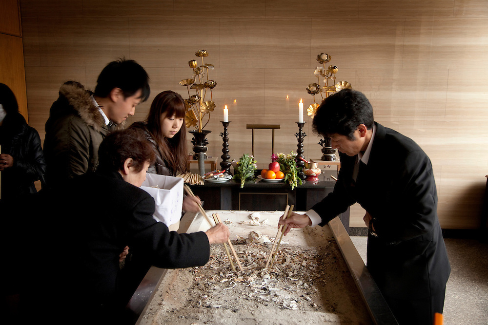 The family of Atsushi Sato, 27, attends his cremation ceremony.  His body was found after the earthquake and tsunami hit the city of Rikuzen Takada on 11 March 2011.