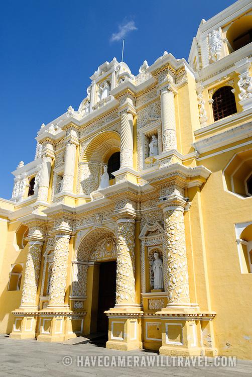 Columns and doorway of the distinctive  and ornate yellow and white exterior of the Iglesia y Convento de Nuestra Senora de la Merced in downtown Antigua, Guatemala.
