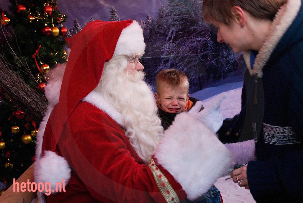 jongetje huilt als hij bij de kerstman op schoot zit...cocacola actie op het van heekplein te enschede