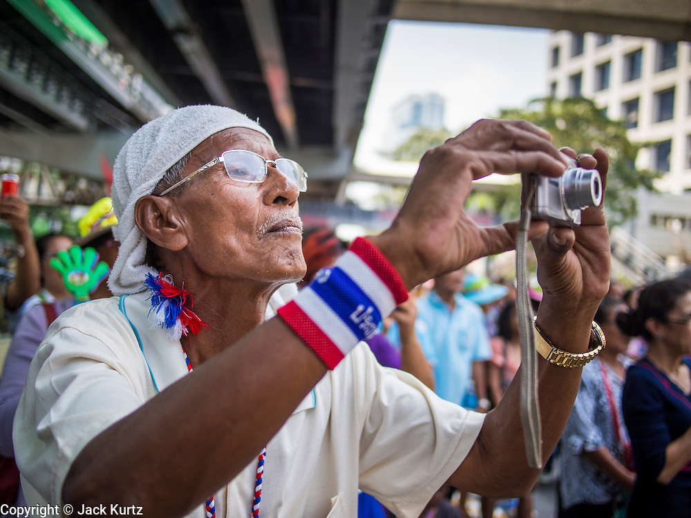 24 FEBRUARY 2014 - BANGKOK, THAILAND: A supporter of Suthep Thaugsuban takes photos of Suthep during a rally the day after several violent attacks on protestors' sites over the weekend. At least four people, three of them children, were killed in political violence over the weekend in Thailand. One in Trat province, near the Cambodian border, and three in Bangkok, at the Ratchaprasong protest site. At the Ratchaprasong site a grenade was fired into a crowd killing a child and an adult. A second child, injured in the blast, died overnight in a Bangkok hospital.   PHOTO BY JACK KURTZ