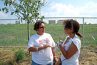 USA, Chicago, August 25, 2009.   Kimberly Wasserman and Lillian Molina discuss LVEJO business next to the fenced-off Celotex Site, possible home for a much-needed park. The Little Village Environmental Justice Organization, headquartered in a predominantly Mexican-American neighborhood of Chicago, campaigns not only against pollution but for clean power, park facilities, urban agriculture, and restoring public transit. LVEJO's staff and volunteers make significant outreach and education efforts, especially for youth. Photo for an HOY feature story by Jay Dunn.