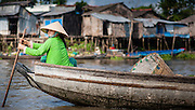 Woman paddling on a boat on Mekong delta (Vietnam)