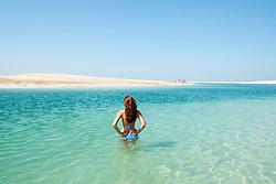 Woman in sea at The Island Lebanon beach resort on a man made island, part of The World off Dubai coast in  United Arab Emirates