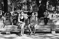 A lady enjoys the last rays of summer while others are engrossed in their mobile devices.