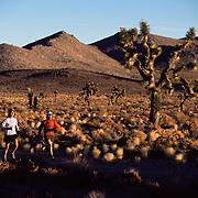 A photo of two women running through Joshua Trees in the desert near Lone Pine, CA.