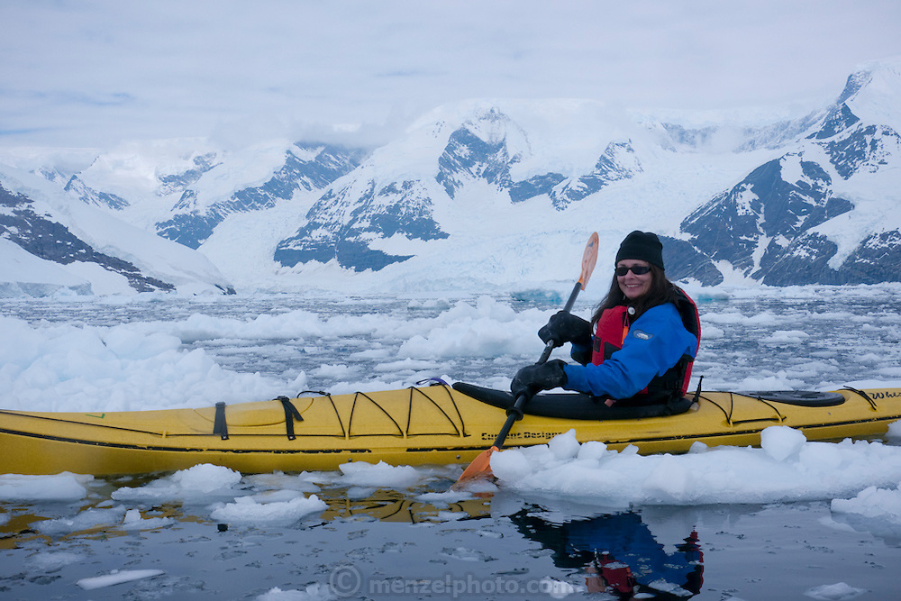 Faith D'aluisio kayaking in Antarctica off the Scandinavian-built ice-breaker Akademik Sergey Vavilov, originally built for the Russian Academy of Science and still used occasionally by scientists. The icebreaker is now predominantly used for adventure touring in both the Arctic and the Antarctic. The ship is currently operated by a Russian crew, and staffed with employees of the adventure touring company Quark Expeditions, and carries around 100 passengers at a time. Skontorp Cove. MODEL RELEASED.