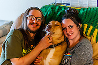 Young couple relaxing at home with their dog, Aurora, Colorado USA.