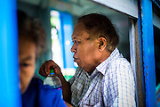 15 JUNE 2013 - YANGON, MYANMAR: A passenger drinks a bottle of water on the Yangon Circular Train. The Yangon Circular Railway is the local commuter rail network that serves the Yangon metropolitan area. Operated by Myanmar Railways, the 45.9-kilometre (28.5 mi) 39-station loop system connects satellite towns and suburban areas to the city. The railway has about 200 coaches, runs 20 times and sells 100,000 to 150,000 tickets daily. The loop, which takes about three hours to complete, is a popular for tourists to see a cross section of life in Yangon. The trains from 3:45 am to 10:15 pm daily. The cost of a ticket for a distance of 15 miles is ten kyats (~nine US cents), and that for over 15 miles is twenty kyats (~18 US cents). Foreigners pay 1 USD (Kyat not accepted), regardless of the length of the journey.     PHOTO BY JACK KURTZ