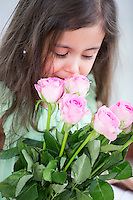 Cute girl smelling roses at home