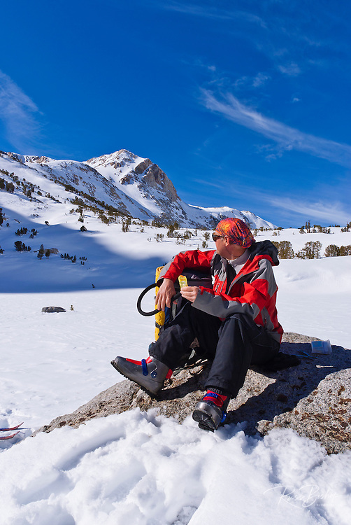 Backcountry skier taking a break on the way to Piute Pass, Inyo National Forest, Sierra Nevada Mountains, California