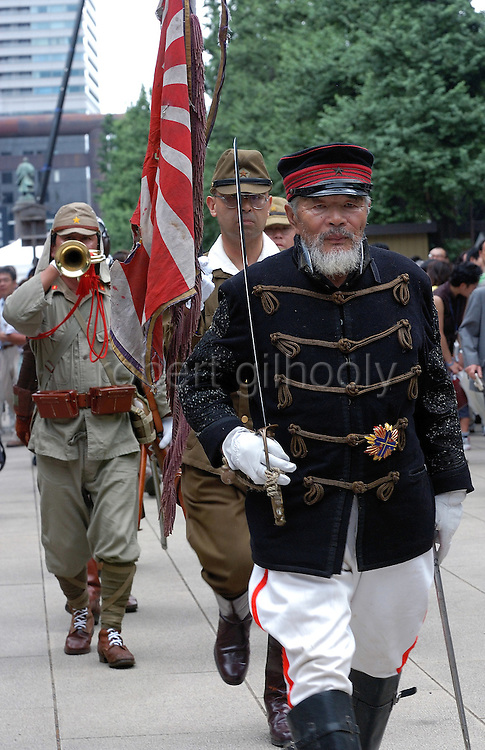 Japanese nationalists dressed in WWII uniforms and Edo-period military attire enter the grounds of Yasukuni Shrine in Tokyo, Japan. very year on August 15, the day Japan officially surrendered in WWII, tens of thousands of Japanese visit the controversial shrine to pay their respects to the 2.46 million war dead enshrined there, the majority of which are soldiers and others killed in WWII and including 14 Class A convicted war criminals, such as Japan's war-time prime minister Hideki Tojo. Each year speculation escalates as to whether the country's political leaders will visit the shrine, the last to do so being Junichiro Koizumi in 2005. Nationalism in Japan is reportedly on the rise, while sentiment against the nation by countries that suffered from Japan's wartime brutality, such as China, has been further aggravated by Japan's insistence on glossing over its wartime atrocities in school text books...Photographer:Robert Gilhooly..