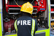 London Fire Brigade, station training session. Fire fighters put  the hoses back on the fire engine.