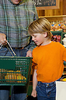 Young boy looking at shopping basket with grandfather in market