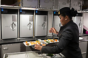 A member of Qatar Airways cabin crew prepares Business Class meals in the rear galley of an Airbus A350-1000 at the Farnborough Airshow, on 18th July 2018, in Farnborough, England.