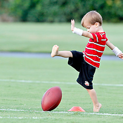 July 28, 2012; Metairie, LA, USA; Baylen Brees son of New Orleans Saints quarterback Drew Brees (not pictured) attempts to kick a football on the field following training camp practice at the team's practice facility. Mandatory Credit: Derick E. Hingle-US PRESSWIRE