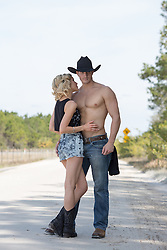 muscular shirtless cowboy and a sexy blonde girl together outdoors