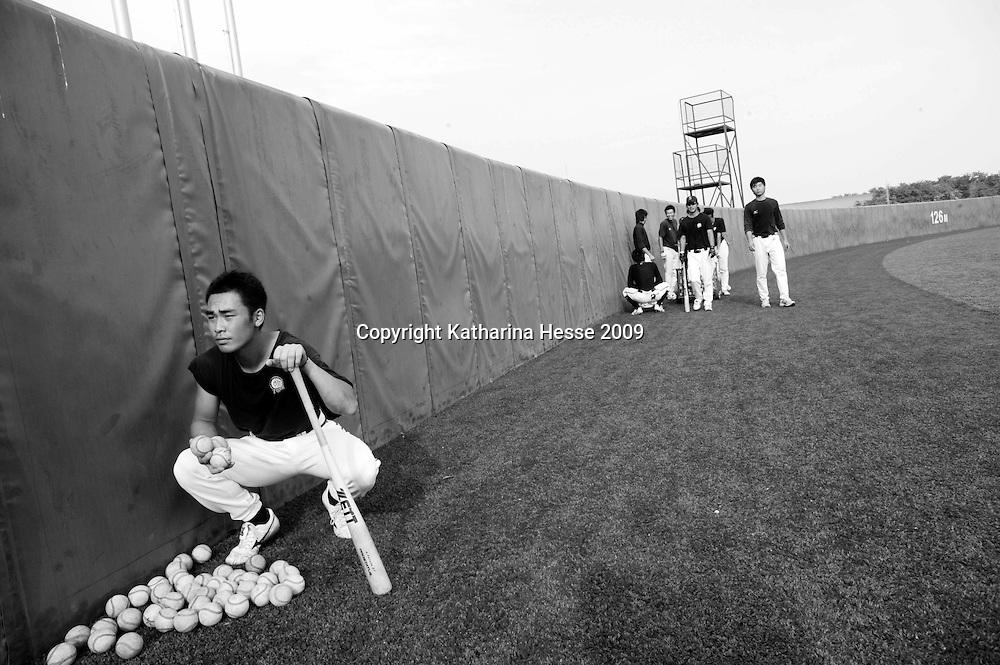 BEIJING, JULY -19: apprentice players pick up the balls in the field, Beijing, July 19, 2007.