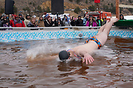 NEDERLAND, CO - MARCH 10: A man jumps into icy brown water in the Frozen Dead Guy Days Polar Plunge competition at the event on March 10, 2018 in Nederland, Colorado. The Frozen Dead Guy Days festival is in honor of Bredo Morstol, who is frozen on dry ice and housed in a shed above the town. (Photo by Rick T. Wilking/Getty Images)