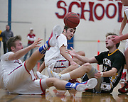 Jamie Wolmering and Matthew Keenan of Fairport, and Jay Sarkis of Greece Athena fight for a loose ball during a game at Fairport High School on Saturday, January 3, 2015.
