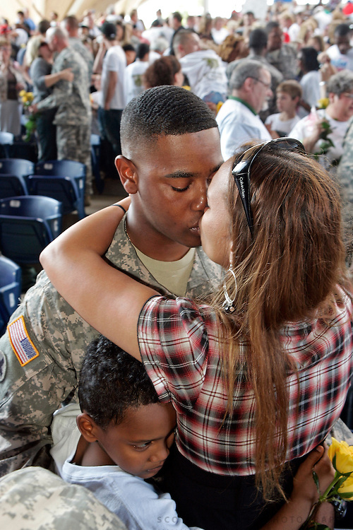 RaeShawn Harris kisses his wife Brandy Harris as their son Jaylen Harris, 7, all of Rockford, hugs them both Thursday, Sept. 10, 2009, during a welcome home ceremony for the 135th Chemical Company at Rock Valley College's Bengt Sjostrom Theatre in Rockford.<br /> SCOTT MORGAN | ROCKFORD REGISTER STAR