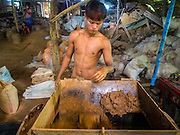 02 NOVEMBER 2014 - TWANTE, YANGON DIVISION, MYANMAR: A worker mixes clay in a pottery factory in Twante, Myanmar. Twante, about 20 miles from Yangon, is best known for its traditional pottery. The pottery makers are struggling to keep workers in their sheds though. As Myanmar opens up to outside investments and its economy expands, young people are moving to Yangon to take jobs in the better paying tourist industry or in the factories that are springing up around Yangon.    PHOTO BY JACK KURTZ