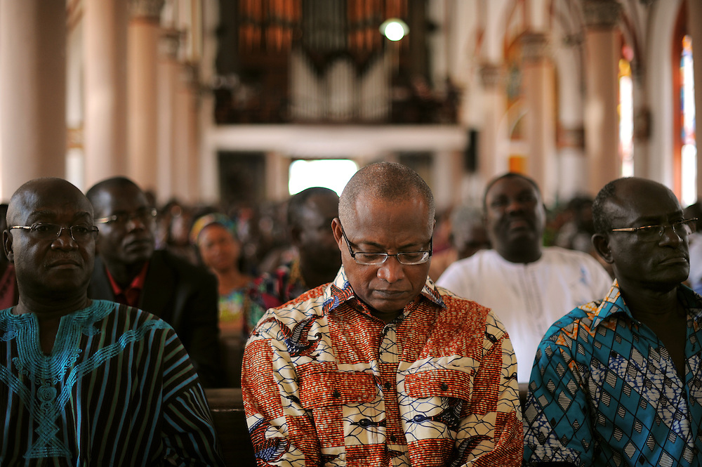 LOME, TOGO  13-02-14   -  Opposition leaders Jean-Pierre Fabre, centre, and Zeus Ajavon, right, at a memorial mass at the Sacred Heart Cathedral in Lome. One month after fire engulfed Lome's Grand Marche, Togolese opposition members and civilians gathered the Sacred Heart Cathedral, a block away from the Grand Marche, to pray for the shopkeepers who lost everything in the blaze.  Photo by Daniel Hayduk