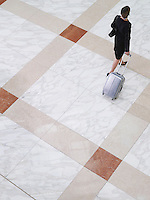 Business woman walking with suitcase elevated view back view