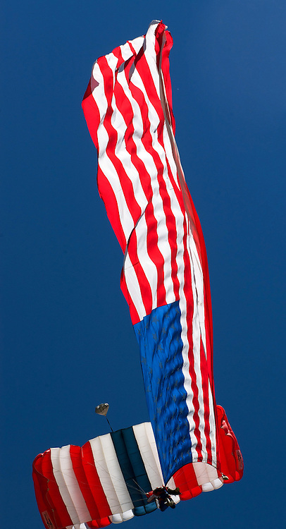A skydiver parachutes down with a giant American Flag at a Colorado Event.