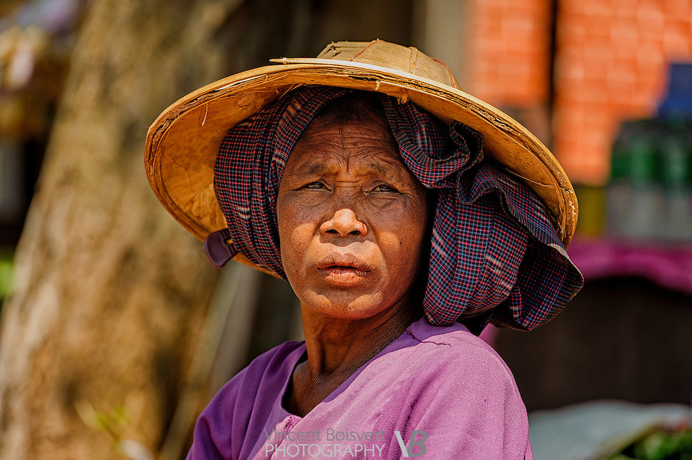 a Shan woman wearing a purple longyis and a straw hat on a market day in kalaw, myanmar
