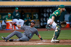 OAKLAND, CA - MAY 25:  David Peralta #6 of the Arizona Diamondbacks slides into home plate to score a run past Jonathan Lucroy #21 of the Oakland Athletics during the third inning at the Oakland Coliseum on May 25, 2018 in Oakland, California. The Arizona Diamondbacks defeated the Oakland Athletics 7-1. (Photo by Jason O. Watson/Getty Images) *** Local Caption *** David Peralta; Jonathan Lucroy