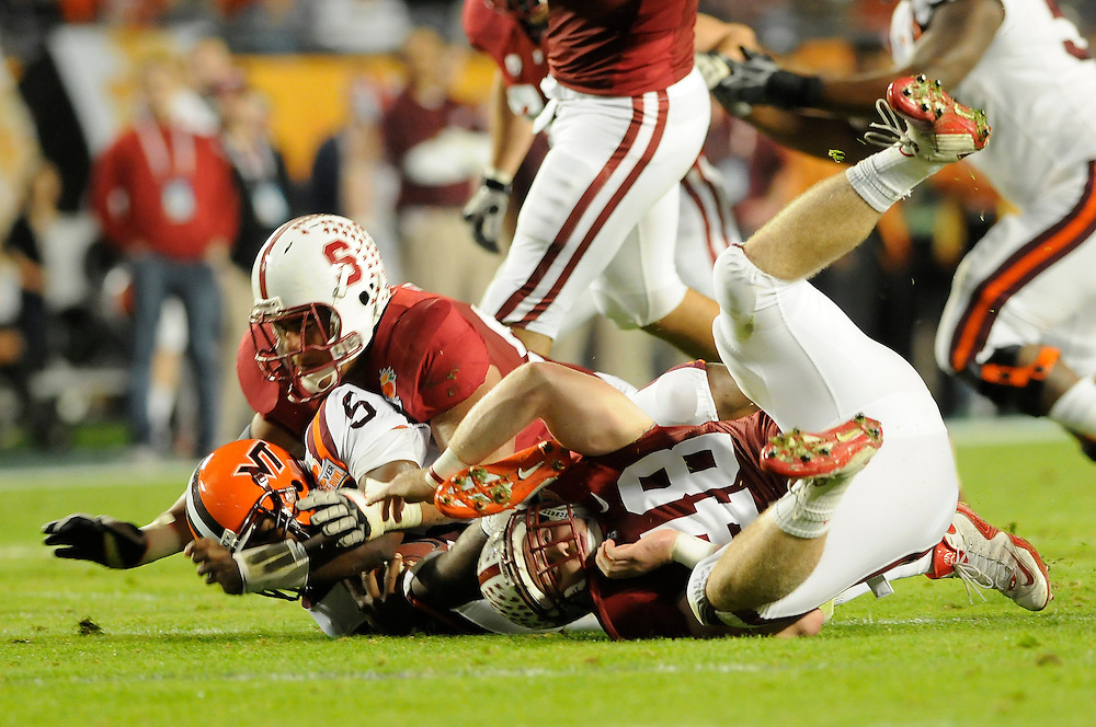 January 3, 2011: Tyrod Taylor of the Virginia Tech Hokies is sacked by Sione Fua (92) and Owen Marecic (48) of the Stanford Cardinal during the NCAA football game between the Stanford Cardinal and the Virginia Tech Hokies at the 2011 Orange Bowl in Miami Gardens, Florida. Stanford led Virginia Tech 13-12 at the half.